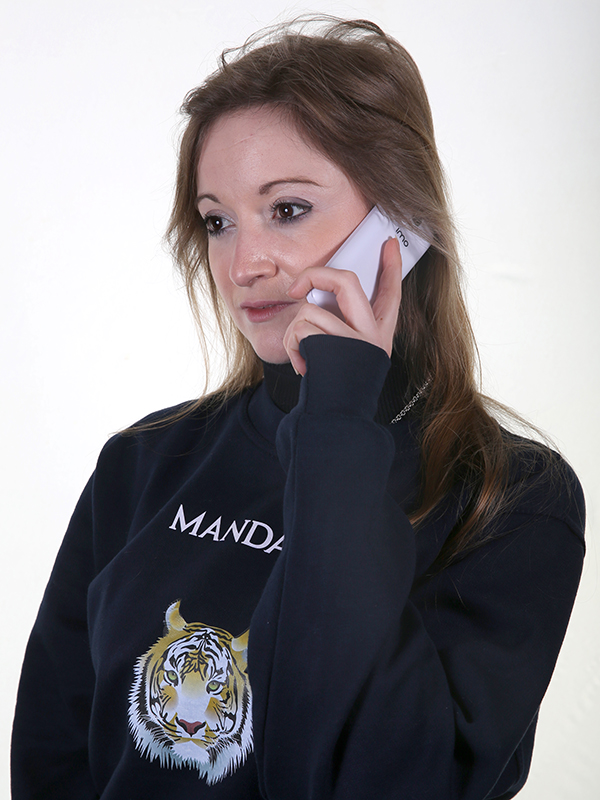 Photograph of young woman wearing a branded navy sweatshirt holding a mobile phone to her ear