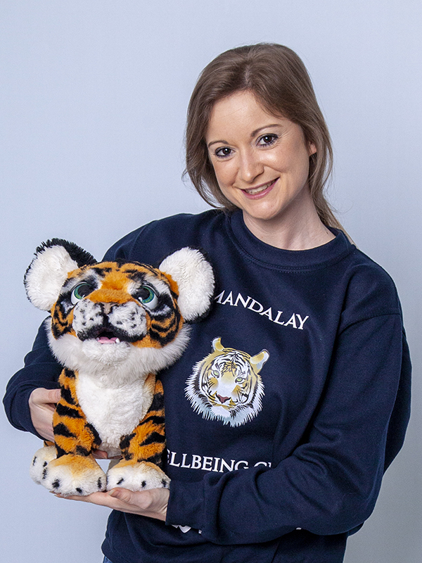 Photograph of young woman in branded Mandalay Wellbeing CIC sweatshirt cradling a Tiger soft toy