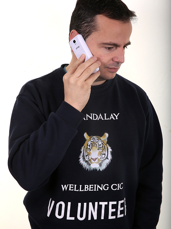 Photograph of a man holding a mobile phone to his ear and wearing a navy Mandalay Wellbeing CIC volunteer sweatshirt