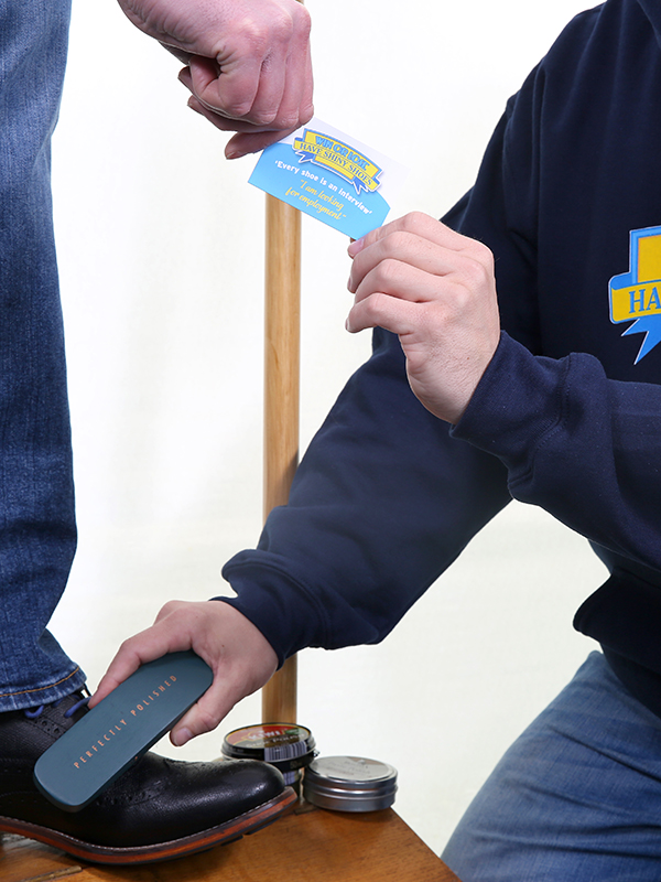 Photograph of person shining shoes and handing their customer a business card
